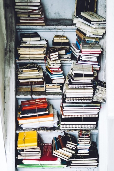 Piles of books on shelves, tied together into bundles. Photo by Simson Petrol on Unsplash