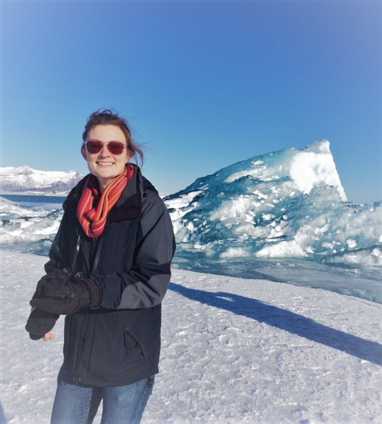 K Chess, a happy woman in sunglasses stands in front of an iceberg.