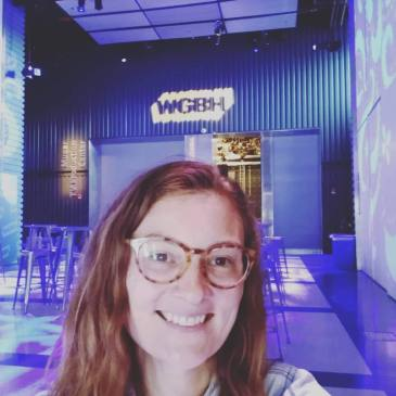 A woman smiles in front of a WGBH logo at a radio studio
